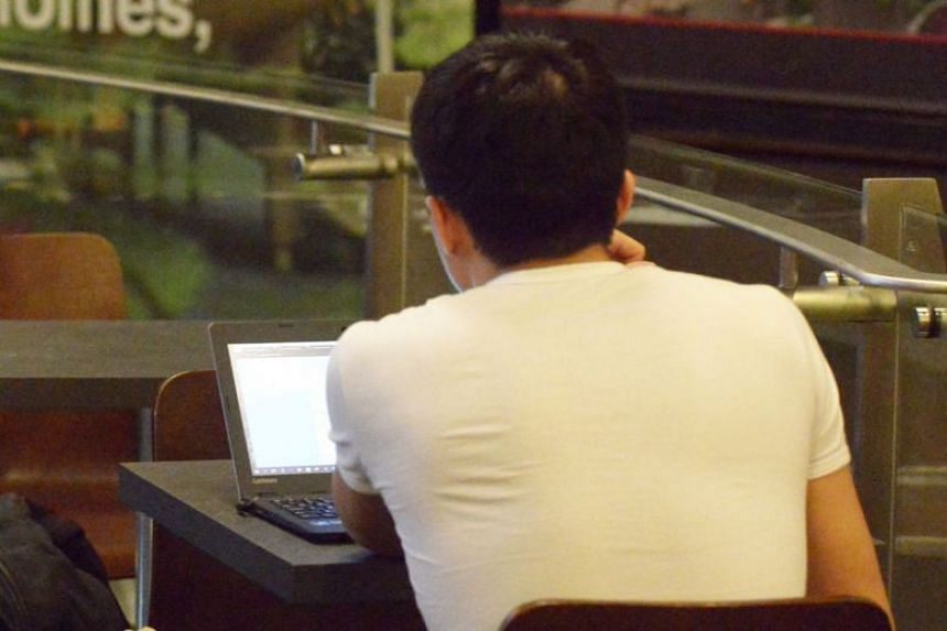 File photo showing a man using a laptop in a cafe. In 2018, victims of online ticket scams either did not receive the tickets or received invalid tickets after payments were made.