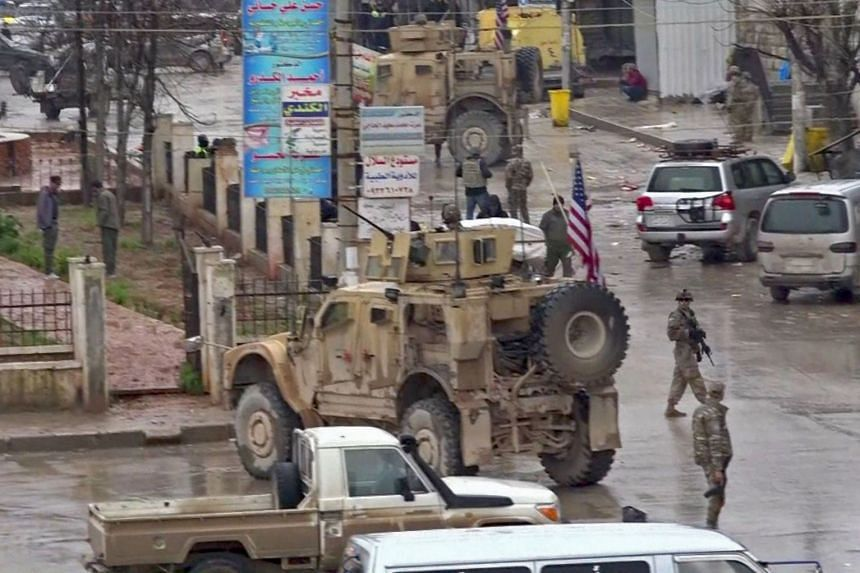An image grab shows US troops gathered at the scene of a suicide attack in the northern Syrian town of Manbij.