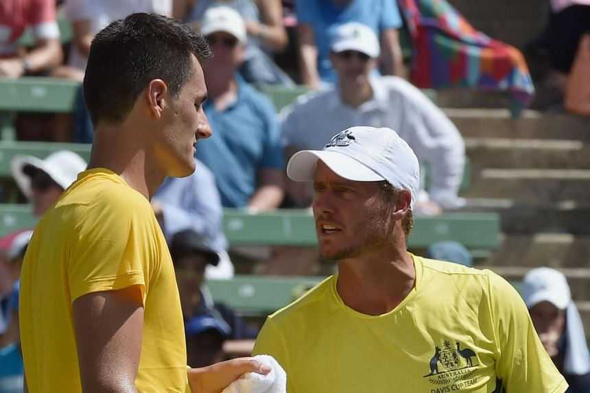 Australia's team captain Lleyton Hewitt (right) encourages compatriot Bernard Tomic between games against Jack Sock of the US during their men's singles match at the World Group first round Davis Cup tennis tournament at Kooyong in Melbourne, on Marc