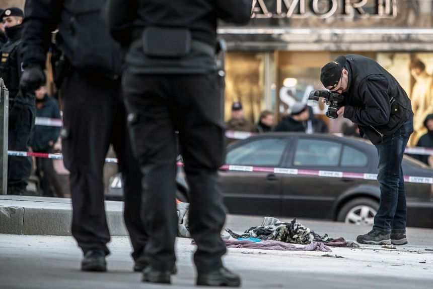 Police officers investigate the scene of where a 54-year-old man tried to set himself on fire at the Wenceslas Square in Prague.