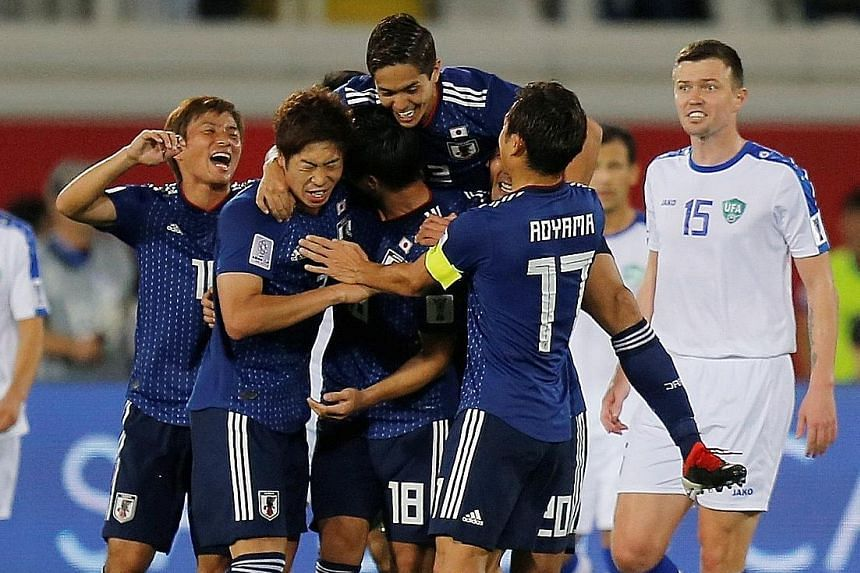Japan celebrating Tsukasa Shiotani's strike from outside the box that gave the Samurai Blue a 2-1 comeback victory over Uzbekistan in their Asian Cup Group F match in Al Ain yesterday. Eldor Shomurodov's solo effort on 40 minutes, his fourth goal of