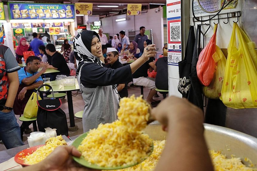 A customer trying out QR code payment at the Geylang Serai Market and Food Centre last September. Under Nets' new initiative, funds from Nets transactions made before 5pm will now be credited to hawkers' bank accounts by 11pm the same day, and procee