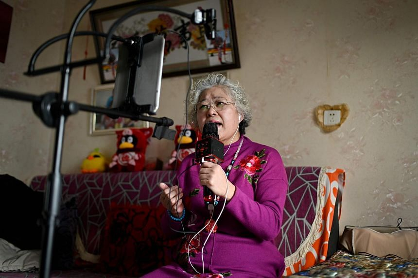 Retiree Wang Jinxiang performing live over the Internet from her home in Beijing.