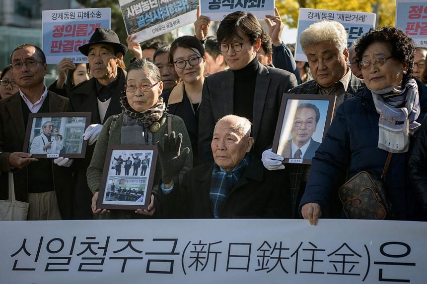 Mr Lee Choon-shik (centre), a victim of forced labour by Japan during its colonial rule of the Korean peninsula from 1910 to 1945, is surrounded by supporters and relatives outside the supreme court in Seoul, on Oct 30, 2018.