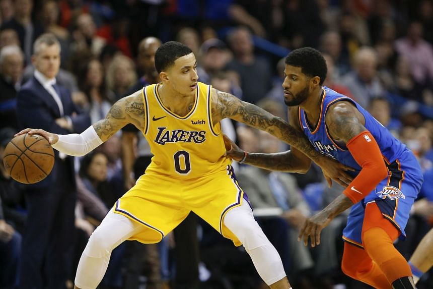 Los Angeles Lakers forward Kyle Kuzma drives to the basket against Oklahoma City Thunder forward Paul George during their NBA game at Chesapeake Energy Arena in Oklahoma City on Jan 17, 2019.