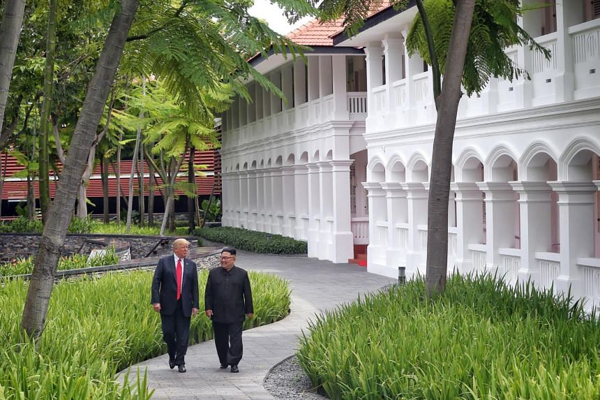 US President Donald Trump and North Korean leader Kim Jong Un strolling through the grounds of the Capella Hotel on Sentosa Island after their working lunch, during their historic summit in Singapore on June 12, 2018.