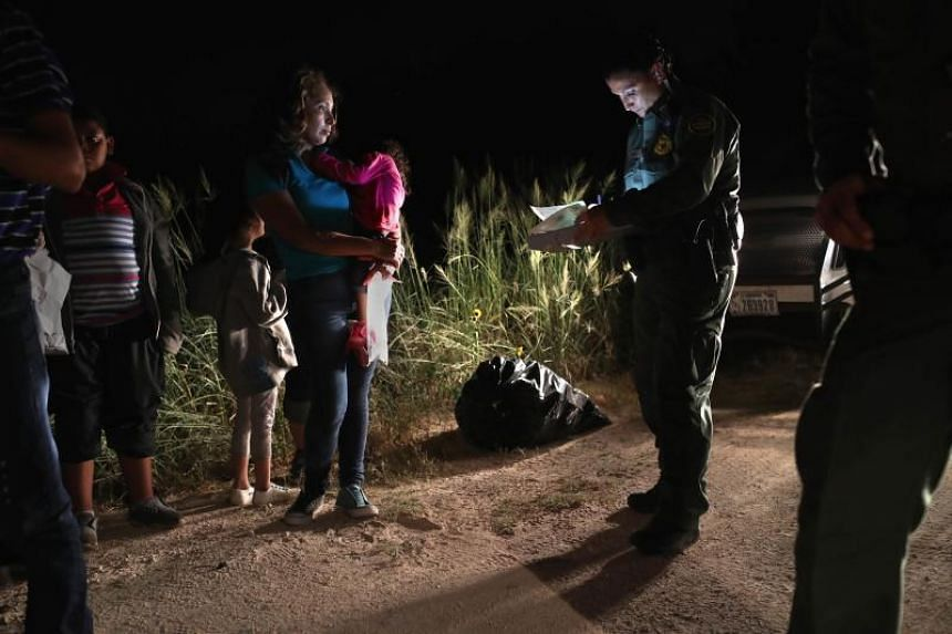 A Honduran mother holds her two-year-old as US Border Patrol agents review their papers near the US-Mexico border in McAllen, Texas, on June 12, 2018 .