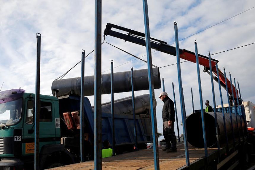 Workers load steels tubes onto a truck, which will be used to protect a deep well next to the area where two-year-old Julen fell into at a private estate in Totalan, southern Spain, on Jan 17, 2019.