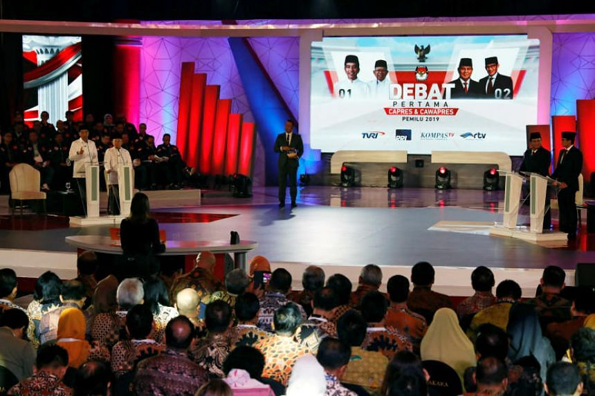 Indonesia's presidential candidate Joko Widodo (left) speaks beside his vice-presidential candidate Ma'ruf Amin during a televised debate with his opponents Prabowo Subianto and his vice- presidential candidate Sandiaga Uno in Jakarta, Indonesia, on