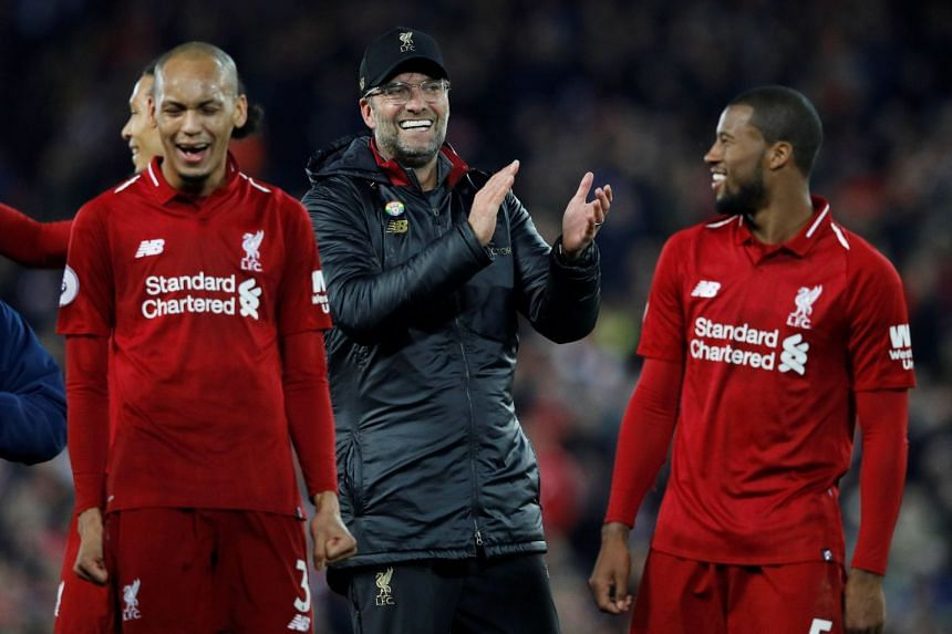 Klopp applauds the fans as Liverpool's Georginio Wijnaldum and Fabinho celebrate at the end of a match.