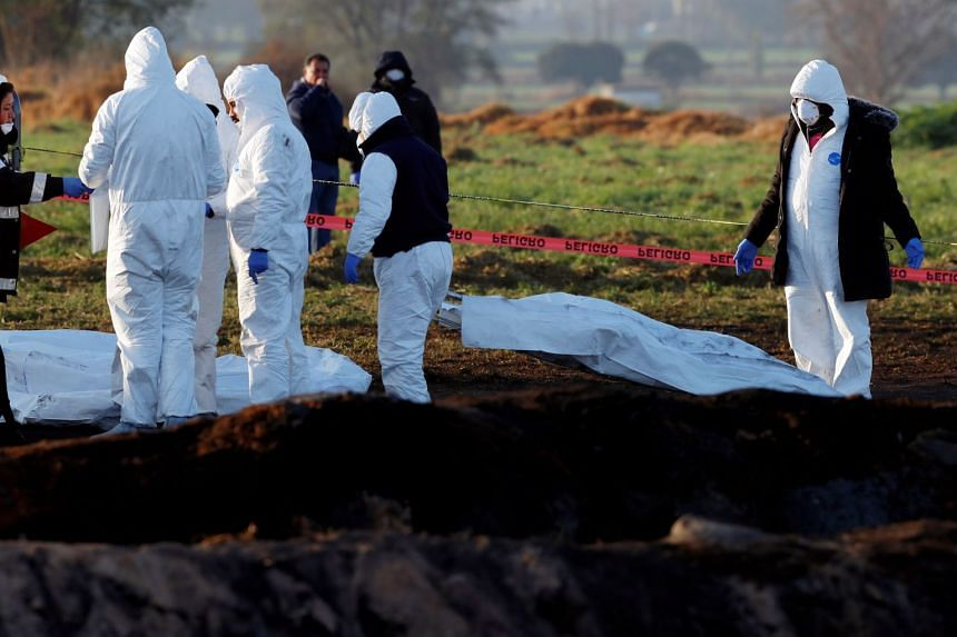 Forensic technicians prepare to remove bodies from the site where the fuel pipeline ruptured.