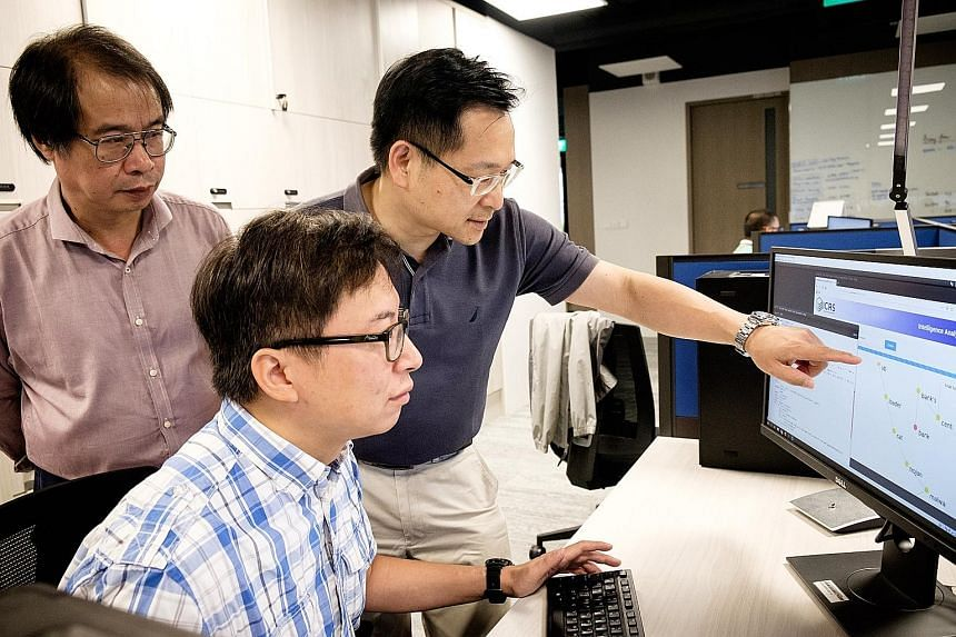 Professor Lam Kwok Yan (in dark blue), senior research engineer Dr Victor Chu (seated), and Associate Professor Wang Huaxiong from Nanyang Technological University, discussing strategies for cyber-security solutions.