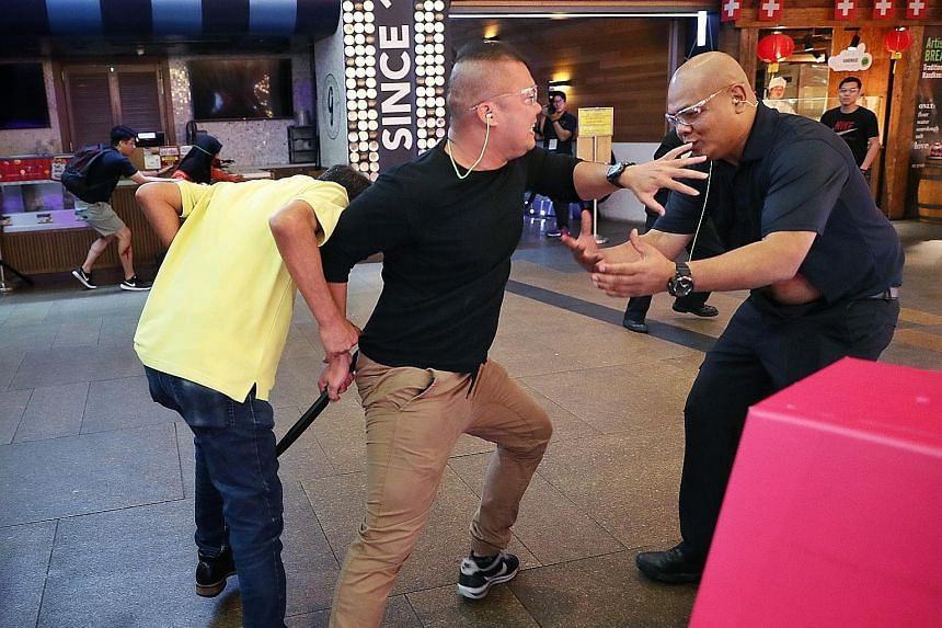 """From above: An """"attacker"""" (centre) trying to """"stab"""" someone during Exercise Heartbeat at 313@Somerset yesterday; members of the Singapore Police Force's Ground Response Force responding to the attack; and Singapore Civil Defence Force officers attend"""