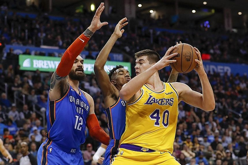 Los Angeles Lakers centre Ivica Zubac, who scored a career-high 26 points, tries to get past centre Steven Adams (12) and guard Terrance Ferguson of the Oklahoma City Thunder in the 138-128 overtime win on Thursday. The Lakers, paced by Kyle Kuzma's