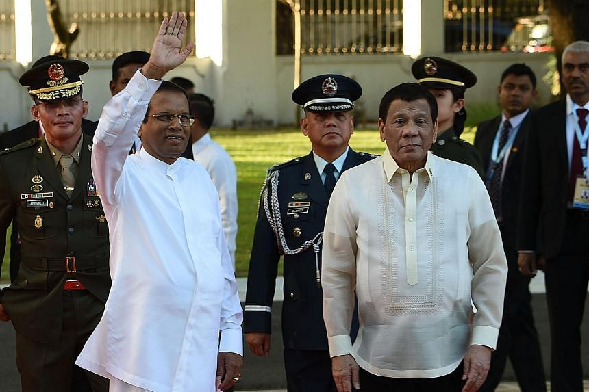 Sri Lankan President Maithripala Sirisena waving as Philippine President Rodrigo Duterte looks on after reviewing a guard of honour during a welcome ceremony at the Malacanang Palace in Manila on Wednesday.