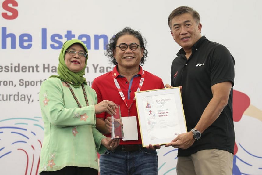 Wheelchair rugby coach Daniel Lee receives his Coaching Inspiration Award from President Halimah Yacob and Sport Singapore CEO Lim Teck Yin at the inaugural SportCares Awards at the Istana on Jan 19, 2019.
