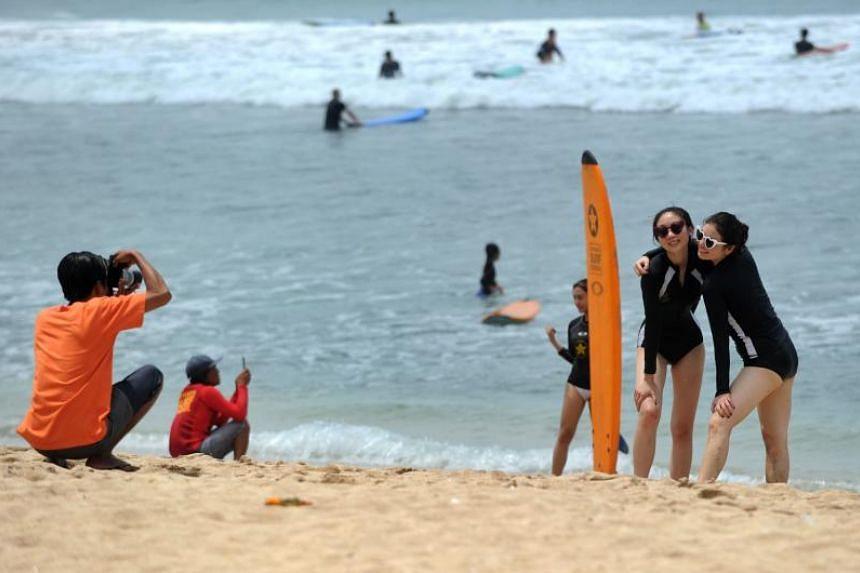 Tourists pose for photographs on Kuta beach on the island of Bali on Jan 4, 2019.