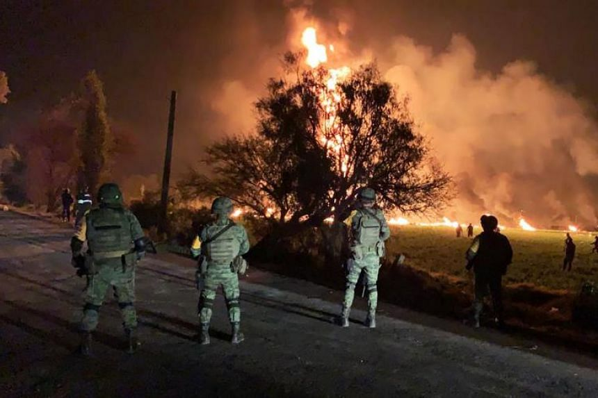 Mexican soldiers standing guard near a fire after a leaking gas pipeline triggered a blaze in Tlahuelilpan, Hidalgo state, on Jan 18, 2019.