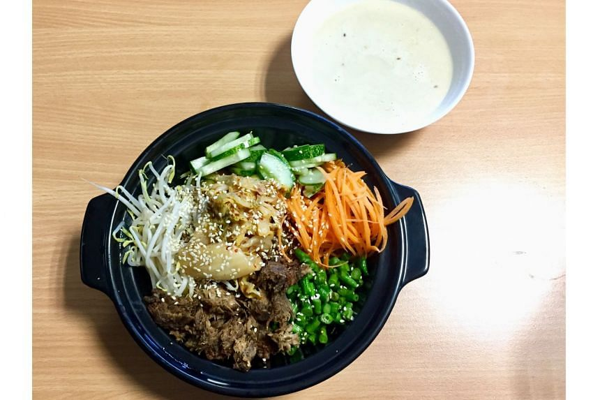 The bibimbap comes with brown rice topped with mushrooms, thinly sliced carrots, bean sprouts, chopped long beans and sliced cucumber.