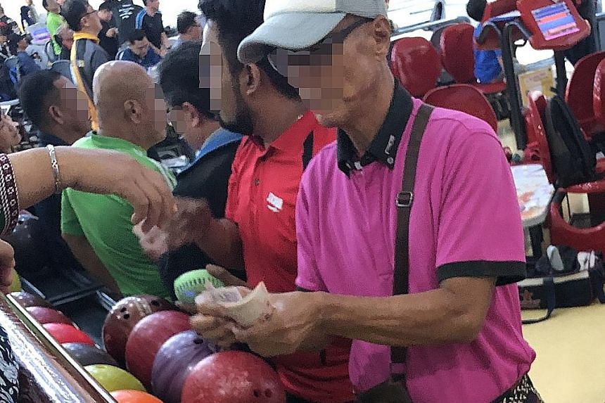 """Above: A man with a wad of cash dealing with a punter at Orchid Bowl @ Orchid Country Club. Left: """"Fans"""" watching the action, with some allegedly placing bets."""