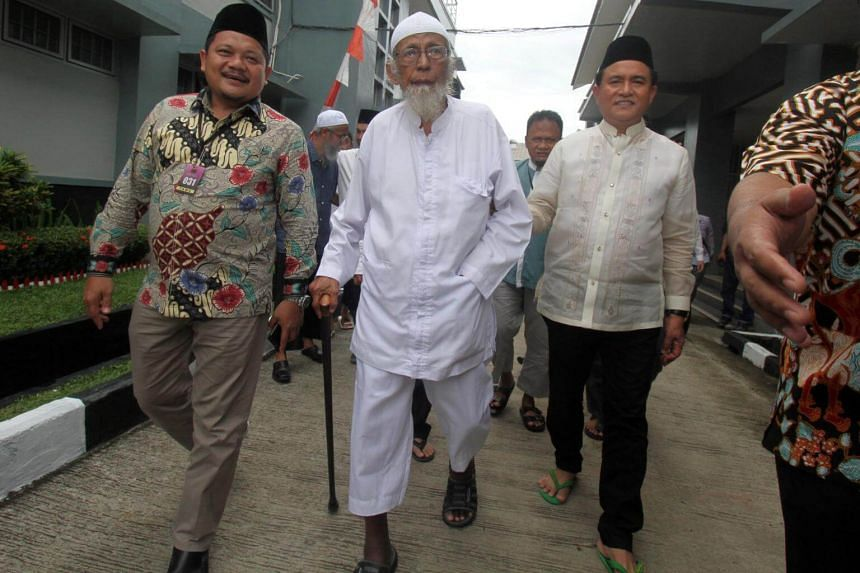 Abu Bakar Bashir (centre), the alleged mastermind of the 2002 Bali bombings, walks as he is visited by Yusril Ihza Mahendra (right), the lawyer for the campaign team of Indonesia's President Joko Widodo and Ma'ruf Amin, at Gunung Sindur prison in Bog