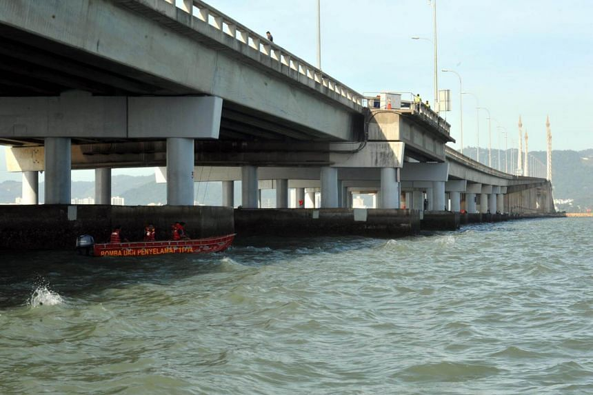 A fire and rescue team searches the waters under Penang Bridge for a car and its passengers which plunged off the bridge after an accident early Sunday (Jan 20) morning.