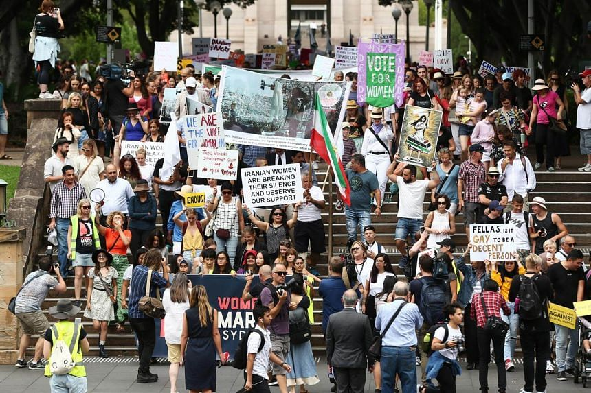 Demonstrators hold signs while marching during the annual Women's March in Sydney, Australia, on Jan 20, 2019.