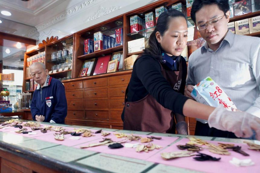 Ms Gu and her husband Hsu Chen-an working at the family's Chinese herbal medicine store in New Taipei City as her father-in-law Hsu Ping-jen looks on.