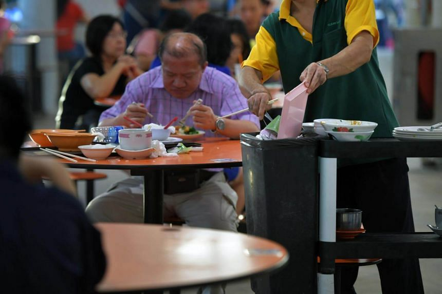 File photo of a cleaner clearing dishes at Bedok Interchange Hawker Centre.