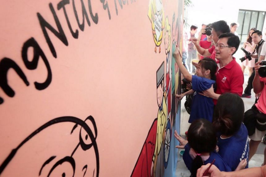Finance Minister Heng Swee Keat carrying Ashlynn Wong, 8, to complete a wall mural that aims to inspire volunteerism in the Tampines community, on Jan 20, 2019.