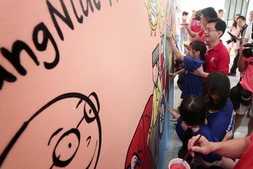 Finance Minister Heng Swee Keat carrying Ashlynn Wong, eight, to complete a mural depicting volunteers in a home, on Jan 20, 2019.