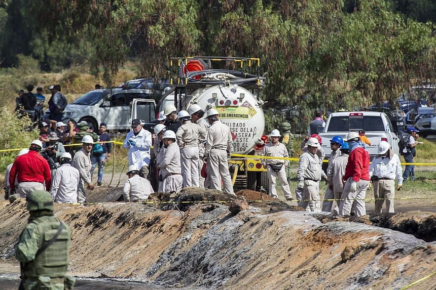 Forensic specialists at the site of the explosion in the central Mexican state of Hidalgo which killed more than 70 people who had rushed to collect petrol from a punctured pipeline last Friday.