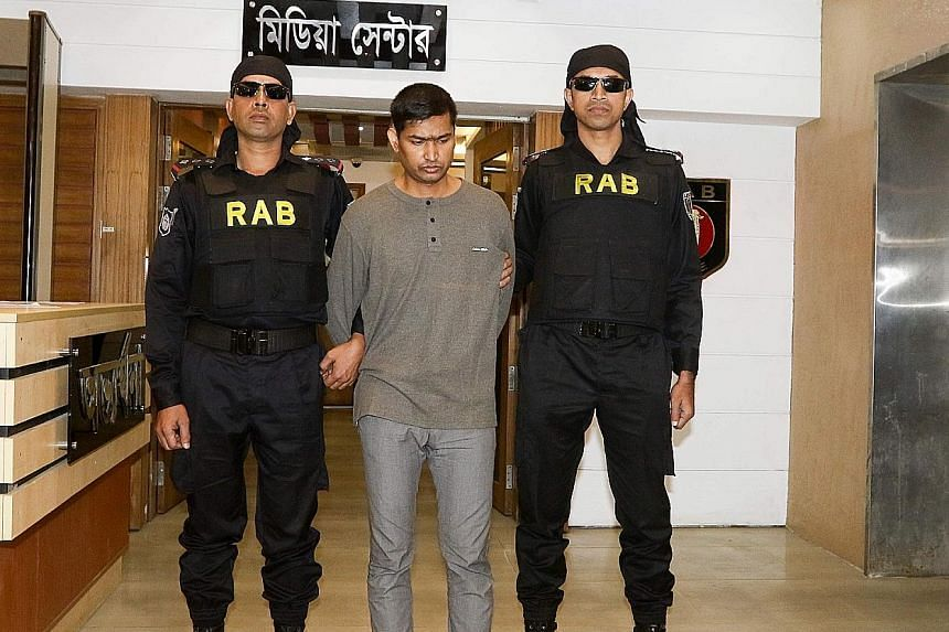 Bangladesh's Rapid Action Battalion officers with Mamunur Rashid, who has been accused of supplying money, arms, ammunition and explosives for a 2016 siege that killed 22 hostages in a Dhaka cafe.
