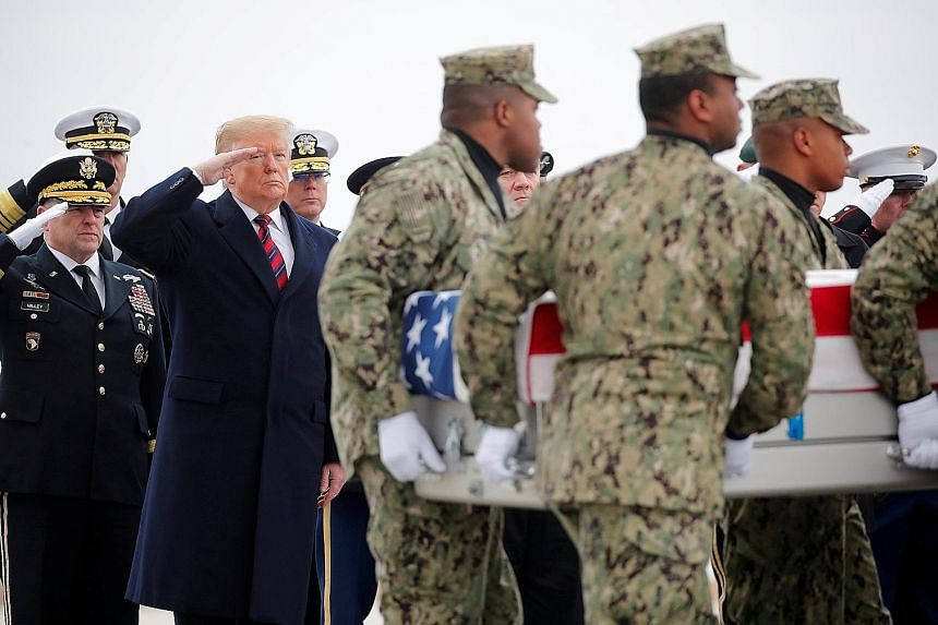 President Donald Trump and his delegation of army and navy officers saluting as a ceremonial team carries a casket bearing Mr Scott Wirtz, a civilian employee of the US Department of Defence, who was killed along with three members of the US military