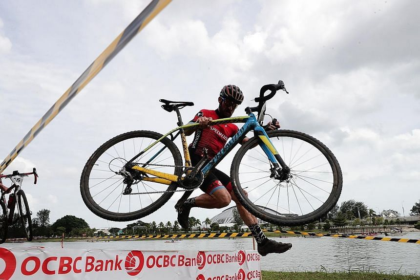 Bastian Dohling of Germany carrying his bike and jumping over one of the six obstacles in the race, en route to winning the Men's Elite category in the OCBC Cycle National Cyclocross Championship yesterday.