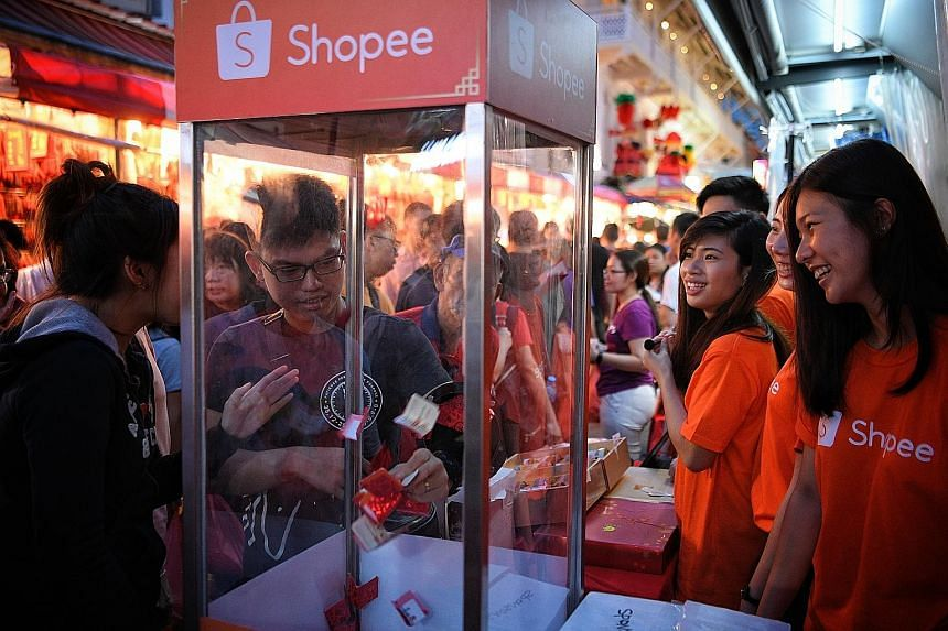 Visitors taking part in a lucky draw at the Shopee booth at the Chinese New Year festive street bazaar in Chinatown yesterday. They can learn first-hand how to shop on the app as well as purchase New Year goodies via the app.