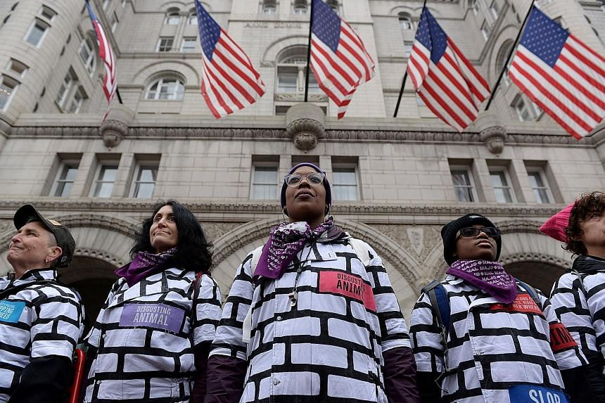 """Protesters in """"wall"""" outfits demonstrating in Washington last Saturday during the third annual women's march. In his first public offer to the Democrats since the government shutdown, US President Donald Trump has offered temporary protections for 70"""