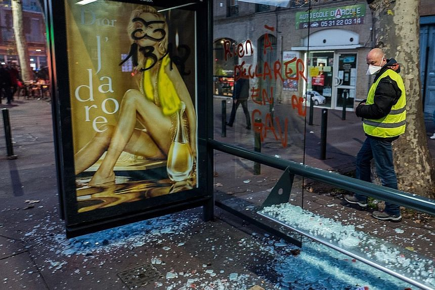 """A """"yellow vest"""" protester looking at a damaged bus-stop in the aftermath of a demonstration in the southern city of Toulouse on Saturday."""