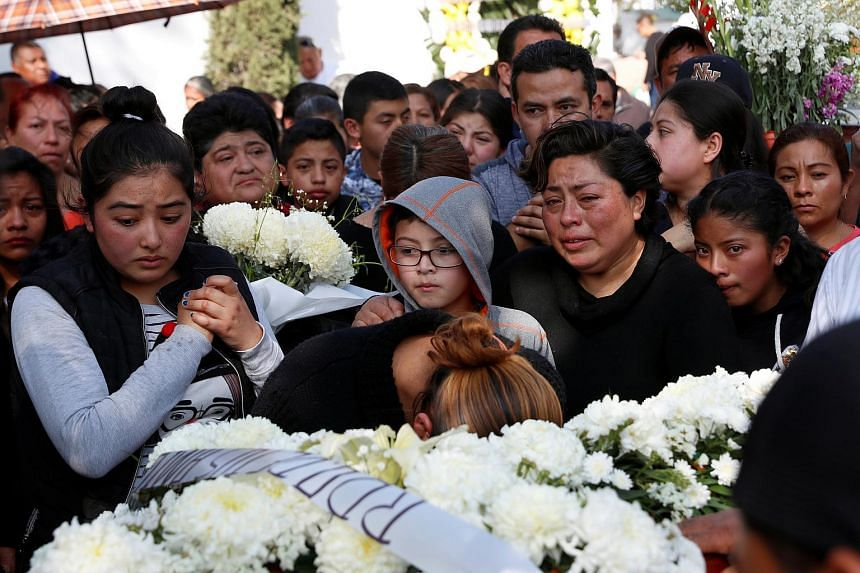 Ms Alicia Moreno (centre), wife of late Cesar Jimenez Brito, 40, who died during the explosion of a fuel pipeline ruptured by oil thieves, cries over his coffin during his funeral service at the cemetery in the municipality of Tlahuelilpan, state of
