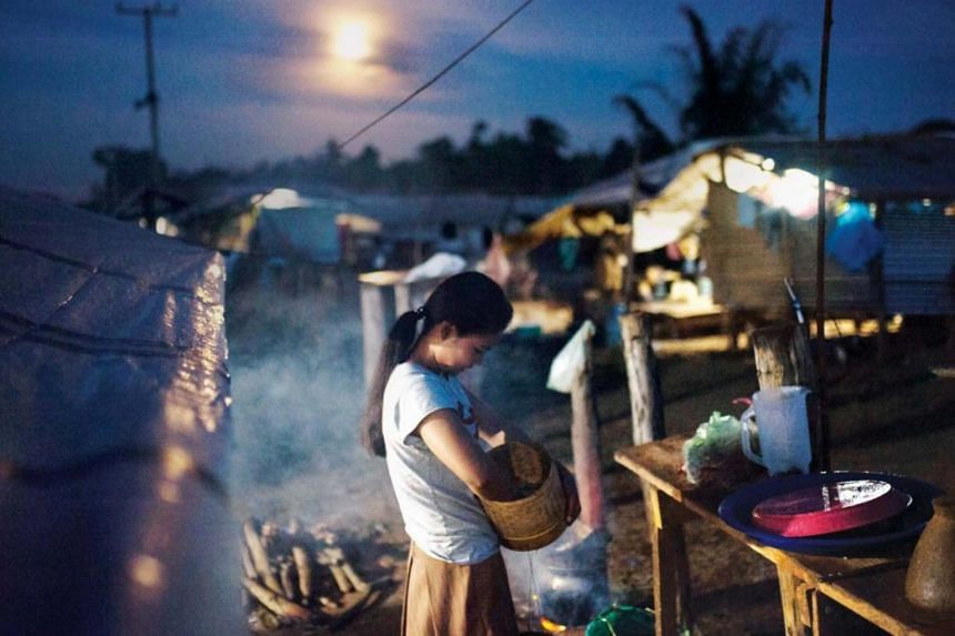 A woman cooks dinner behind her tent in Pindong camp after her home was washed away in the collapse of the dam.