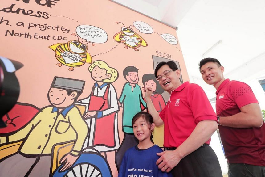 Finance Minister Heng Swee Keat (centre) posing with Ashlynn Wong and Senior Parliamentary Secretary for Transport and Culture, Community and Youth, Mr Baey Yam Keng, posing with a wall mural that aims to inspire volunteerism in the Tampines communit