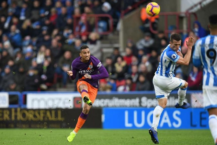 Manchester City's Brazilian defender Danilo (left) shoots past Huddersfield Town's English midfielder Jonathan Hogg but over the bar during the EPL match at the John Smith's stadium in Huddersfield, northern England on Jan 20, 2019.