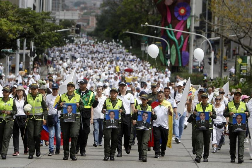 Colombian police and citizens take part in a march against terrorism in Medellin, Colombia, on Jan 20, 2019.