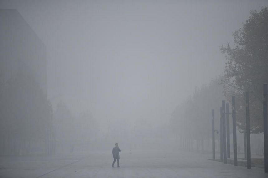A man uses his mobile phone as he walks amid smog in Tianjin, China after the city issued a yellow alert, on Nov 26, 2018.