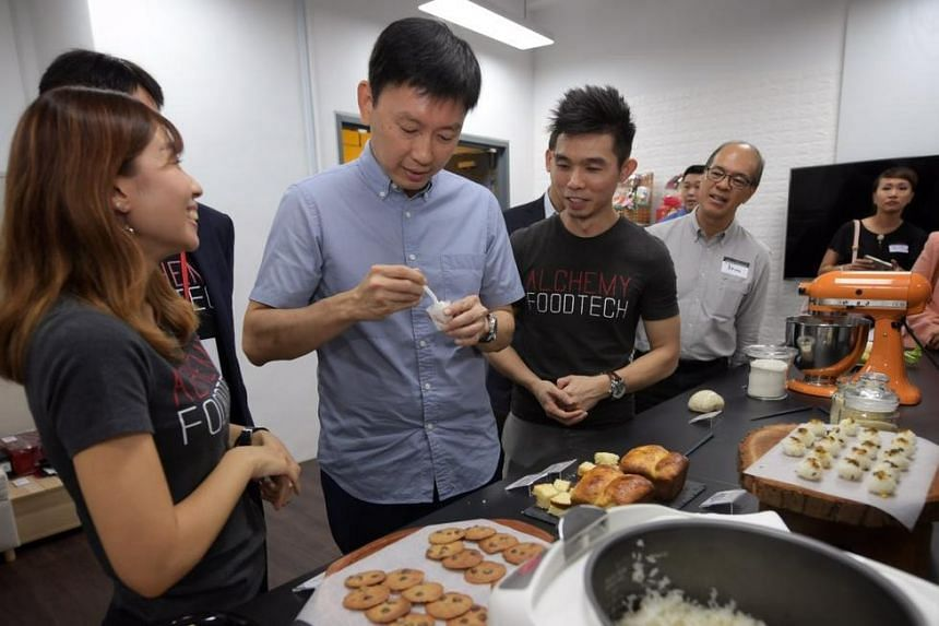 Senior Minister of State, Chee Hong Tat (in blue), tries out white rice that has been modified to have a lower GI at Alchemy Foodtech on Jan 21, 2019.