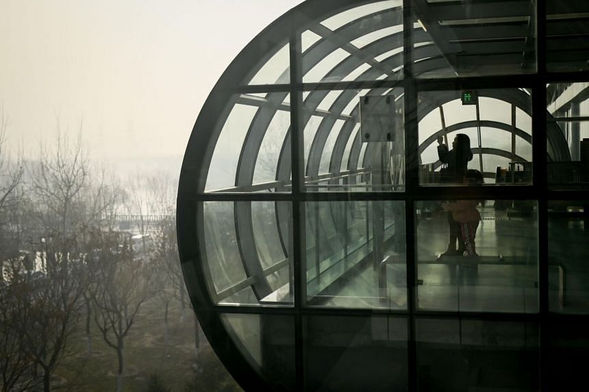 A woman and a young girl look out the windows of a subway station on a polluted day in Beijing on Jan 14, 2019.