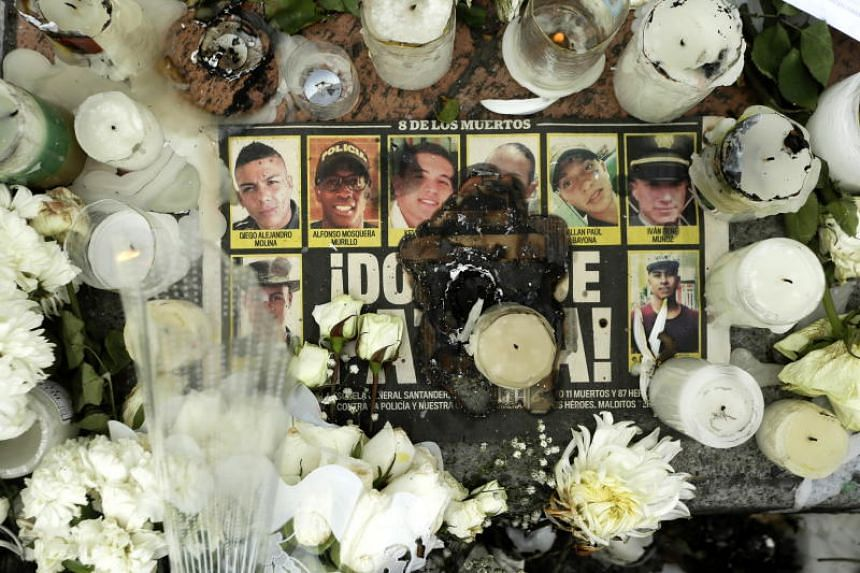 Candles and flowers on a newspaper page with the faces of the victims of the car bomb attack, during a tribute at the police academy in Bogota, Colombia, on Jan 20, 2019.