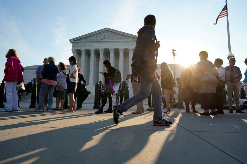 People wait in line to attend the opening day of the new term of the Supreme Court in Washington.