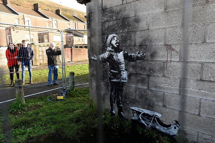 One side of the Season's Greetings mural by street artist Banksy features a child enjoying falling snow that is actually ash from an industrial bin.