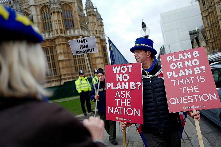Campaigners outside the Houses of Parliament yesterday, before Mrs May spoke on changes to her Brexit withdrawal agreement. A video grab from footage broadcast by the UK Parliament's Parliamentary Recording Unit shows Prime Minister Theresa May makin